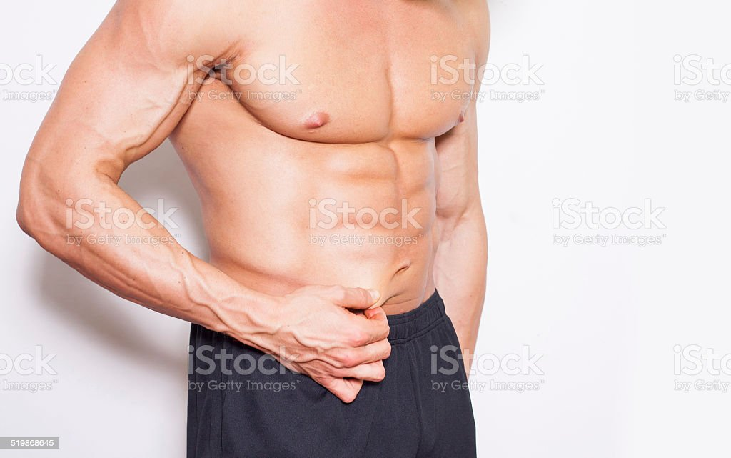 Man's fingers measuring her belly fat. Bodybuilder without shi stock photo