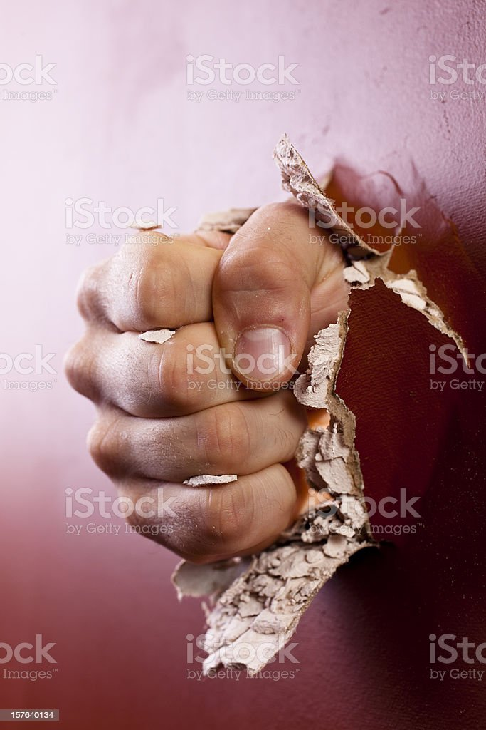 Man's fist coming through wall. royalty-free stock photo