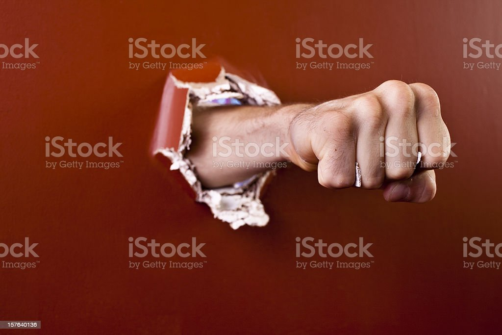 Man's fist coming through wall. stock photo