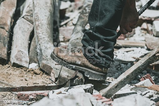 Man's foot with working shoes on a construction site