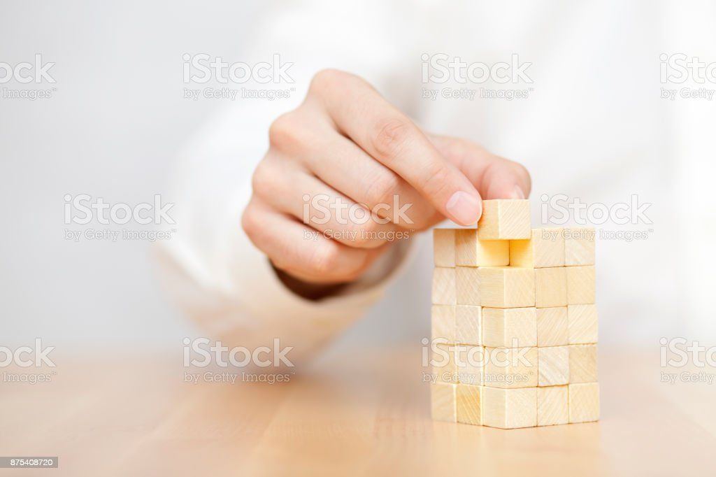 Man's hand adding the last missing wooden block into place. Business success concept. stock photo