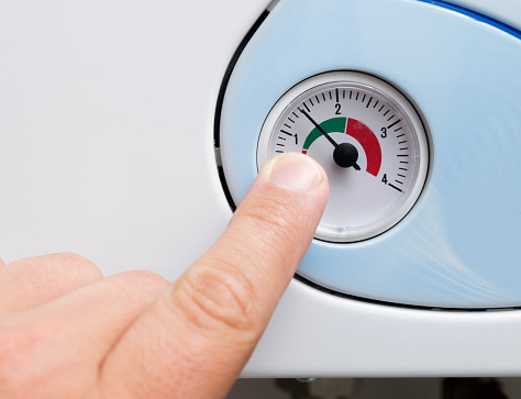 istock Man's hand adjusts the heating boiler 1000997416