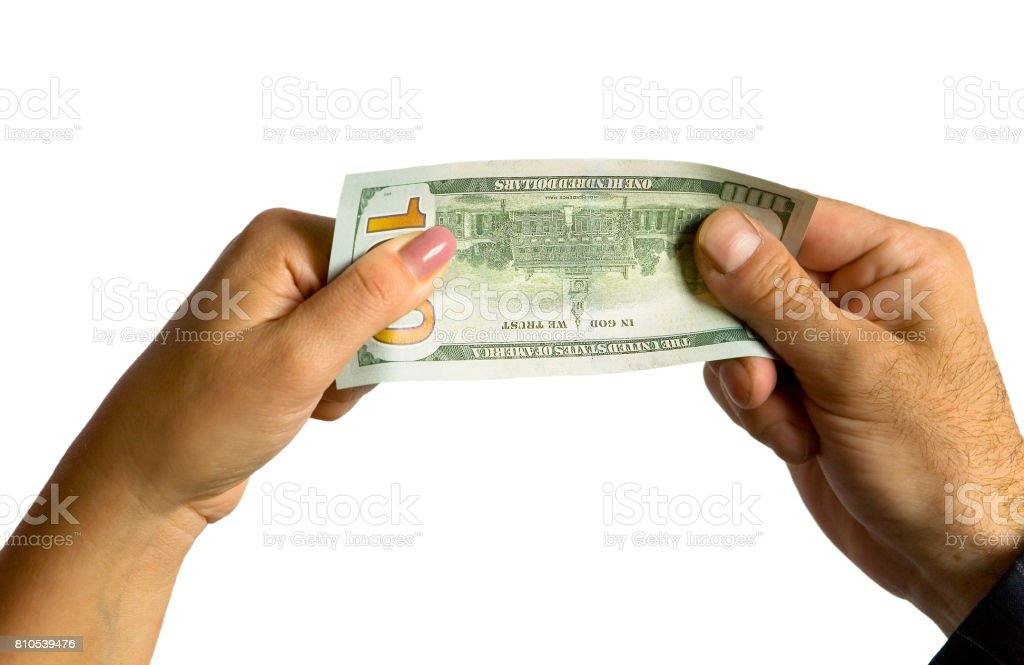 A man's hand and a woman's hand hold a hundred-dollar bill. stock photo