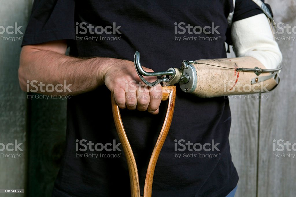 Man's hand and artificial arm holding a shovel's handle. stock photo