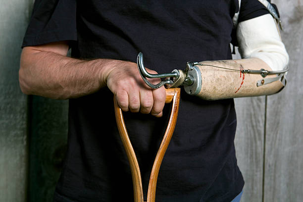 Man's hand and artificial arm holding a shovel's handle. Horizontal close-up of a man with a prosthetic arm holding a handle.  http://i879.photobucket.com/albums/ab359/mikespics1/Working%20People/WorkingPeopleBanner.jpg prosthetic hand stock pictures, royalty-free photos & images