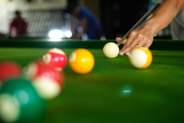 Man's hand and Cue arm playing snooker game or preparing aiming to shoot pool balls on a green billiard table. Colorful snooker balls on green frieze. stock photo