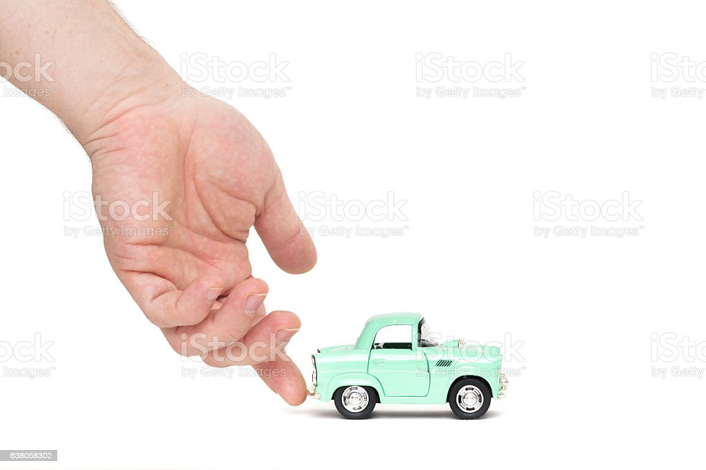 Man's hand assists the cute toy car to drive stock photo