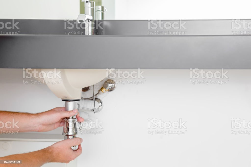 Man\'s hand checking new metal siphon under the sink.