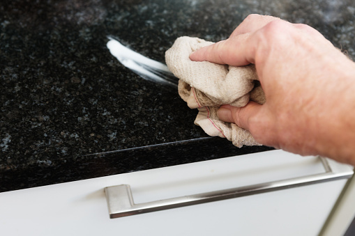 Man's hand cleaning surface in domestic kitchen