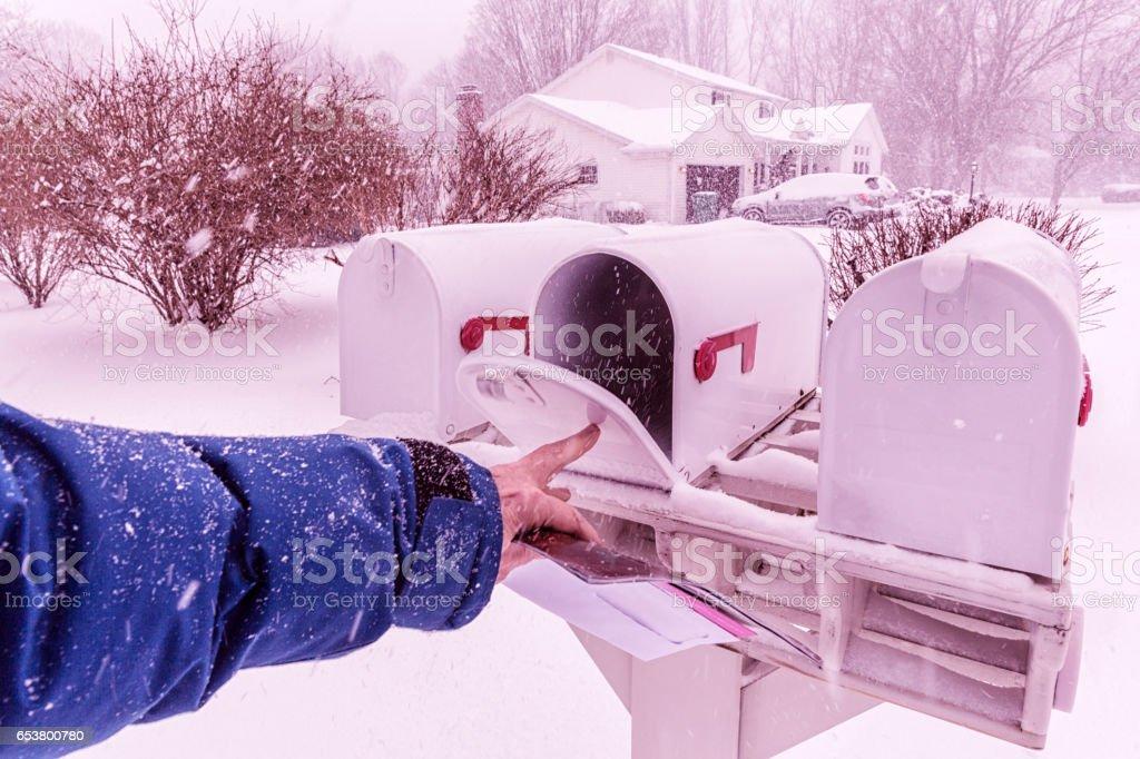 Man's Hand Closing Winter Blizzard Snow Rural Mail Box stock photo