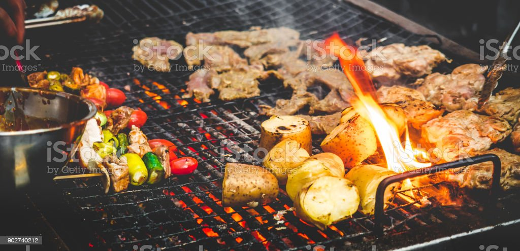 Man's hand cooking grill barbecue/steak with fire stock photo
