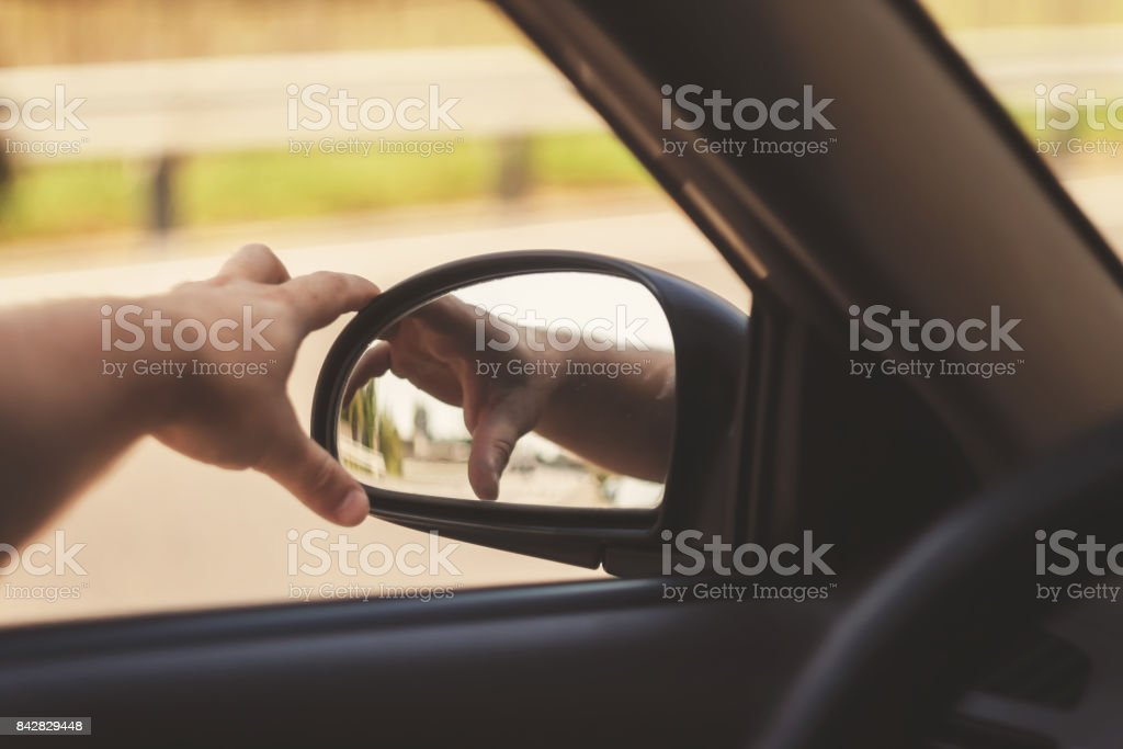 a mão do homem corrige o retrovisor no carro, tonificação retrô - foto de acervo