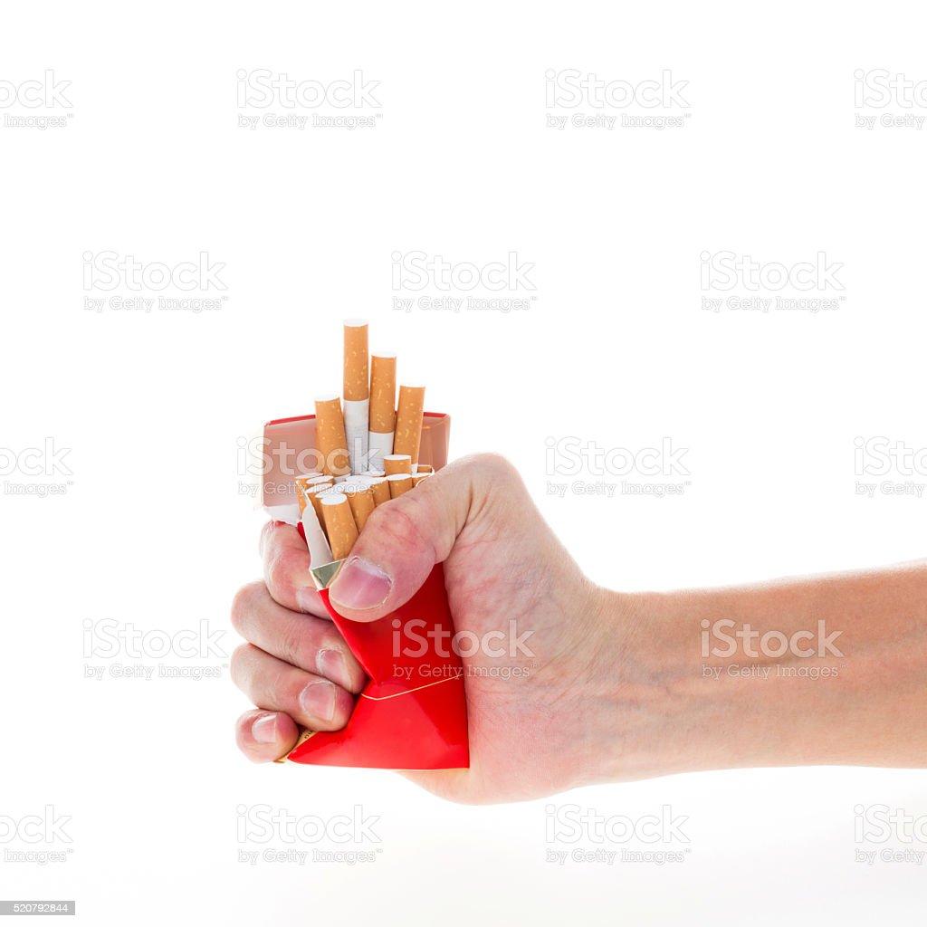 Man's hand crushing cigarette pack stock photo