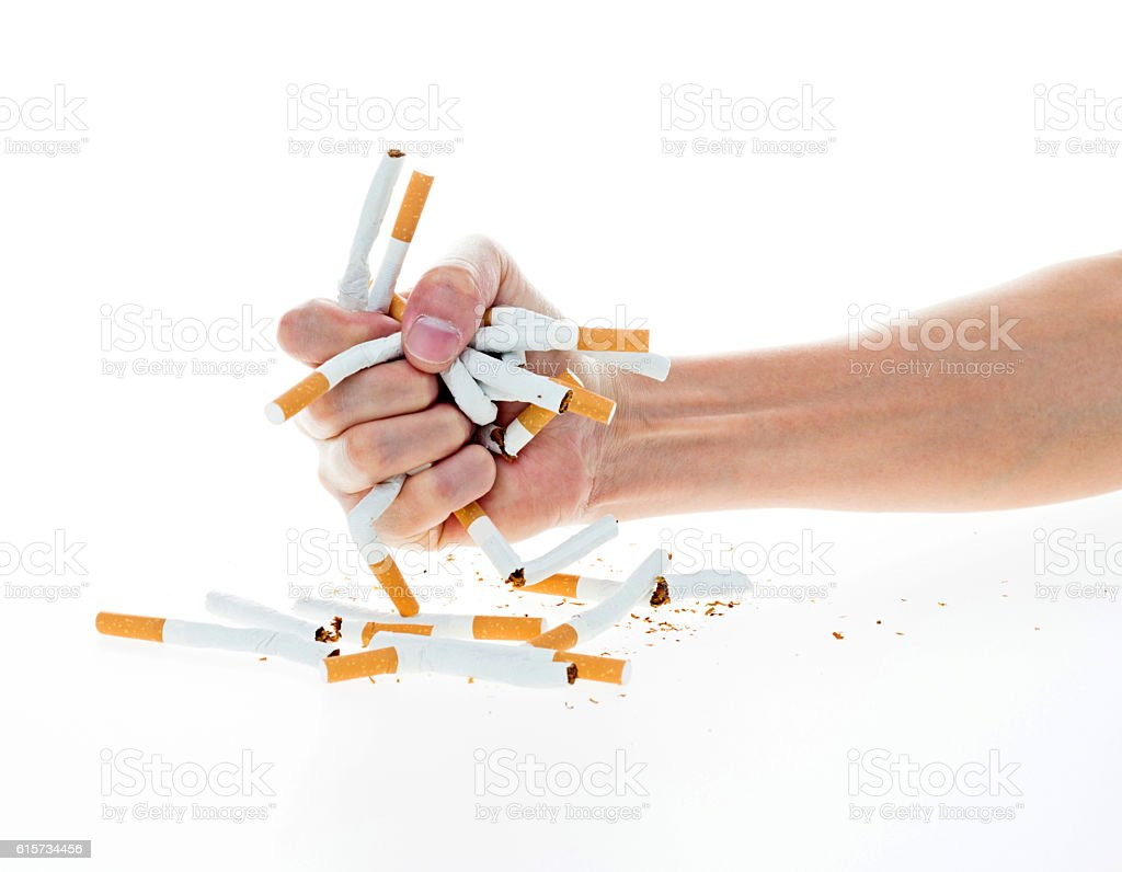 Man's hand crushing cigarettes stock photo