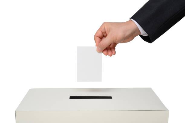 Man's hand down the ballot in the ballot box. stock photo