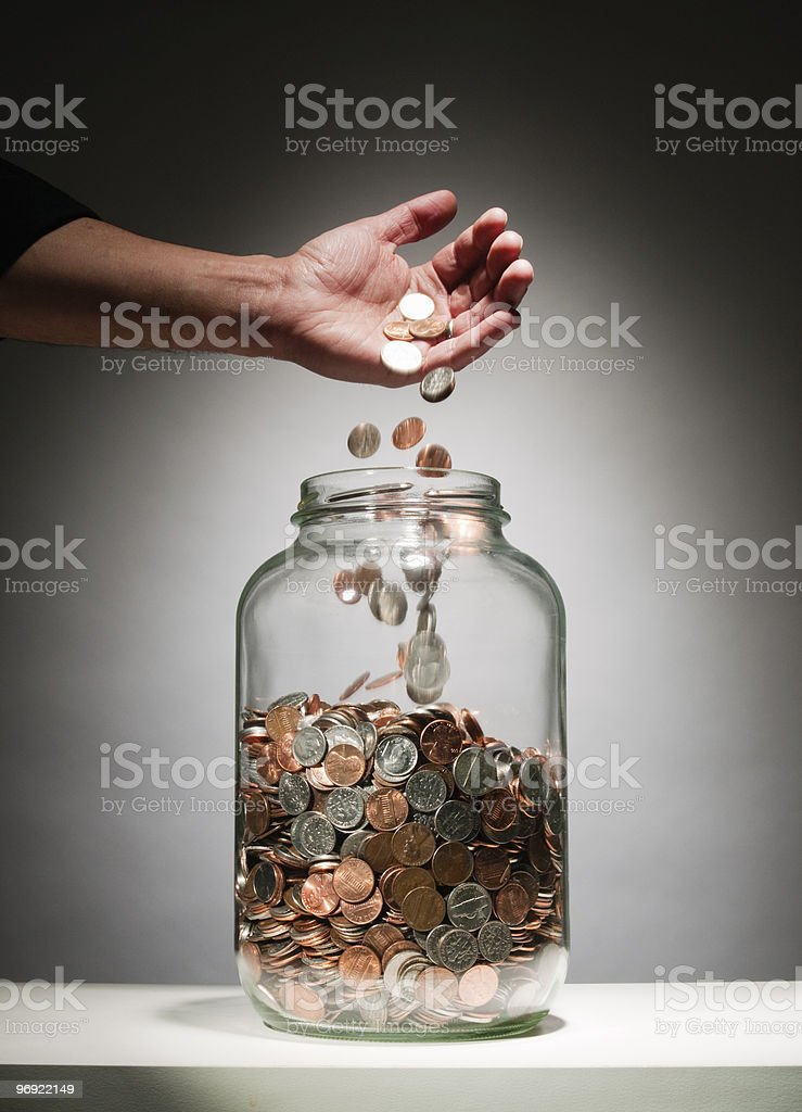 Man's hand dropping coins into jar royalty-free stock photo