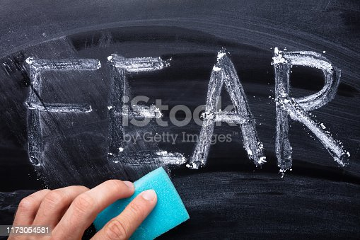 Close-up Of Man's Hand Erasing Fear Word With Blue Sponge On Blackboard