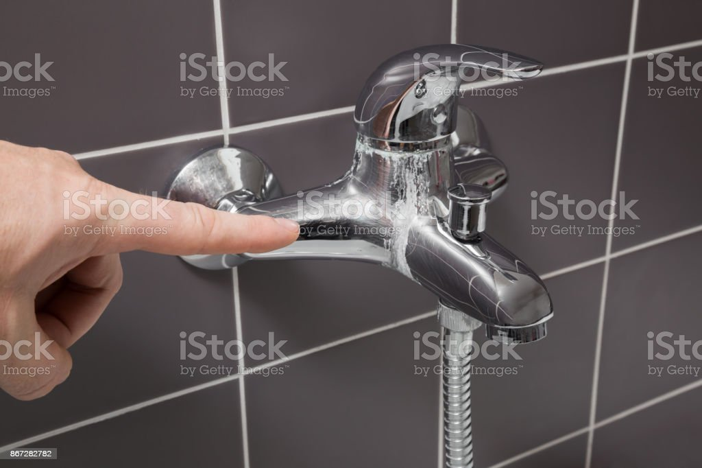 Man's hand finger pointing to calcified water tap in the bathroom. Problem concept. stock photo