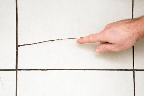 mannes hand fingerzeig auf die gebrochene fliesen auf dem boden. probleme und lösungen gebäudekonzept. - keramik fliesen handwerk stock-fotos und bilder