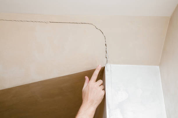 man's hand finger pointing to the cracked wall in house. building problems and solutions concept. - popękany zdjęcia i obrazy z banku zdjęć