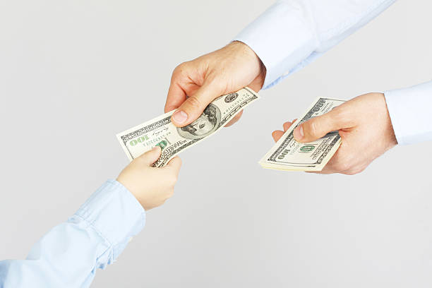 man's hand give money  american hundred dollar bills to boy hand - disbursement stock pictures, royalty-free photos & images