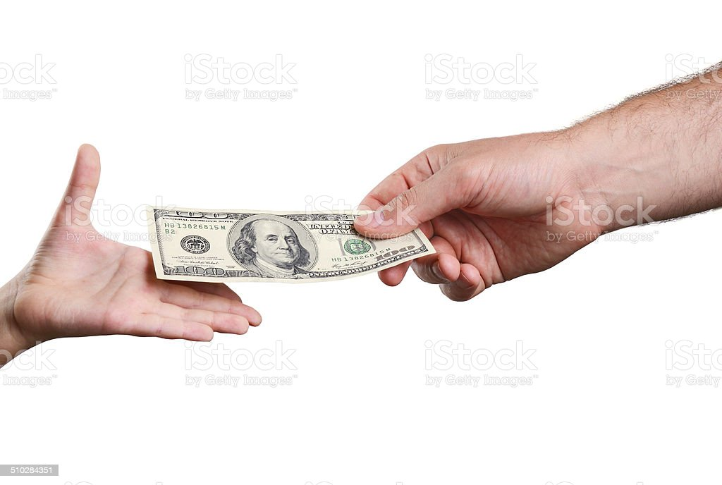 mans hand gives the bill 100 US dollars in childs stock photo