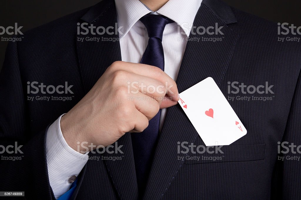 mans hand hiding playing card in suit pocket stock photo