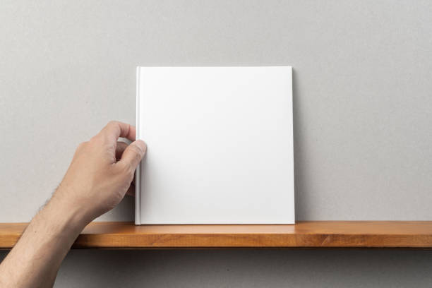 Die Hand des Mannes hält weißes quadratisches Notebook auf Bücherregal – Foto