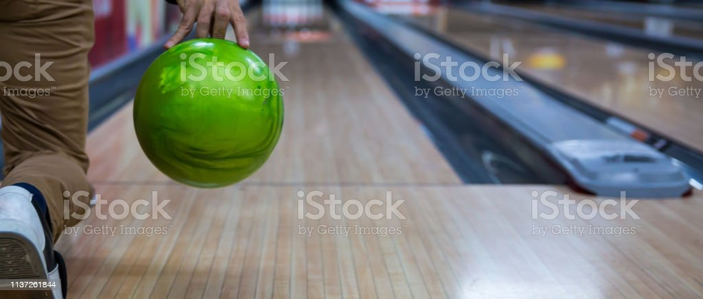Man\'s hand holding a bowling ball ready to throw it.