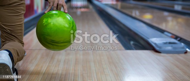 Man's hand holding a bowling ball ready to throw it.