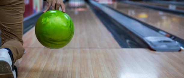 man's hand houden van een bowling bal klaar om het te gooien. jonge man spelen bowling - bowlen stockfoto's en -beelden