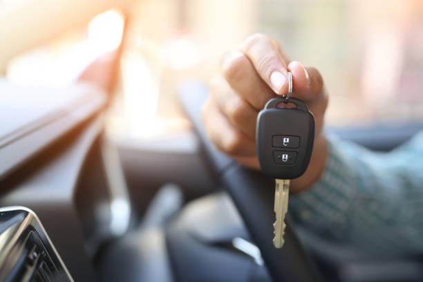 la mano de un hombre sosteniendo la llave de un coche - comprar fotografías e imágenes de stock