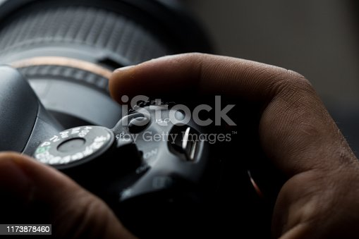 man's hand holding a DSLR camera in dim lighting