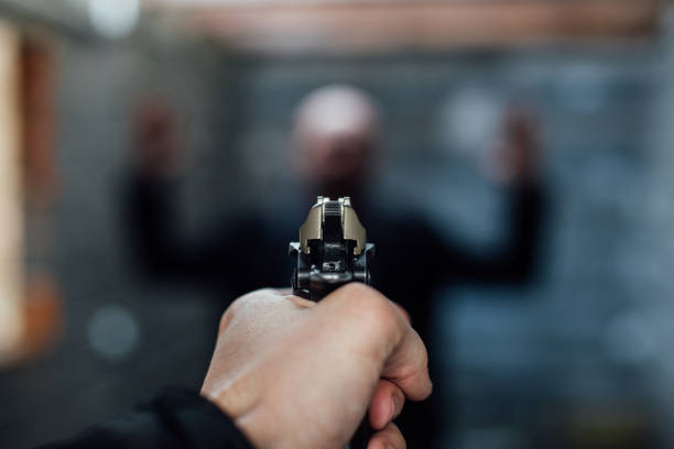A man's hand holding a gun pointed to another man stock photo