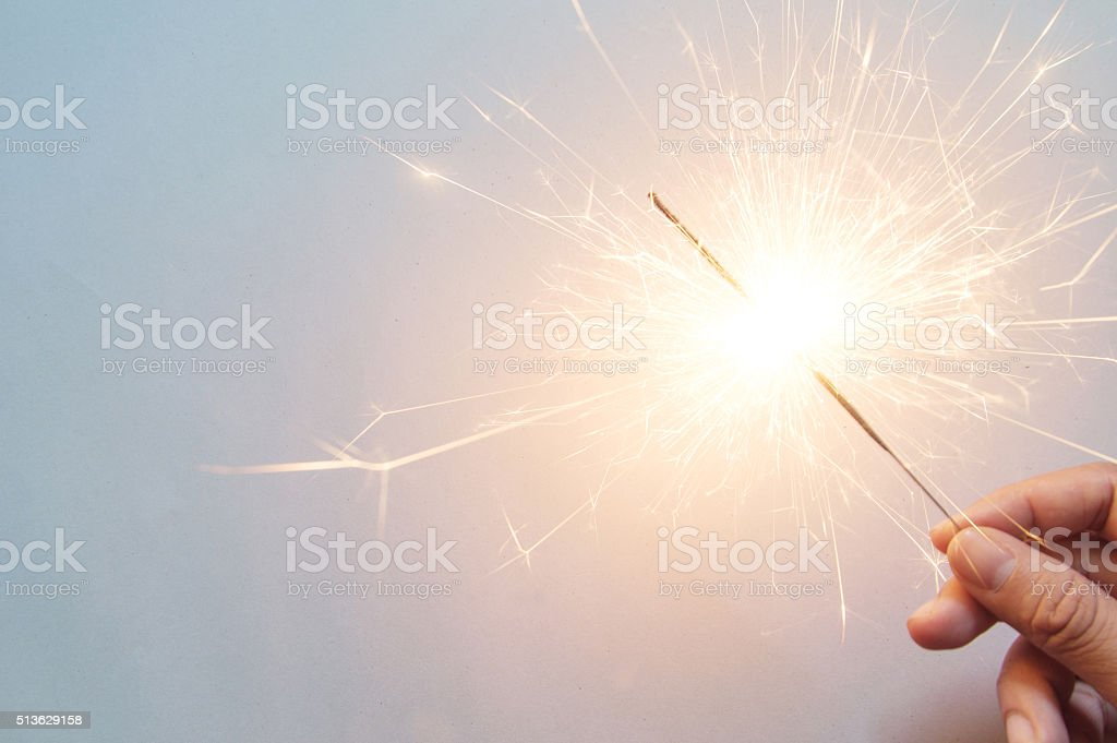 man's hand holding a sparkler stock photo