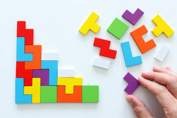 man's hand holding a square tangram puzzle, over wooden table stock photo