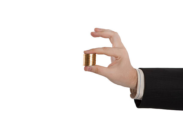 man's hand holding a stack of coins - disbursement stock pictures, royalty-free photos & images