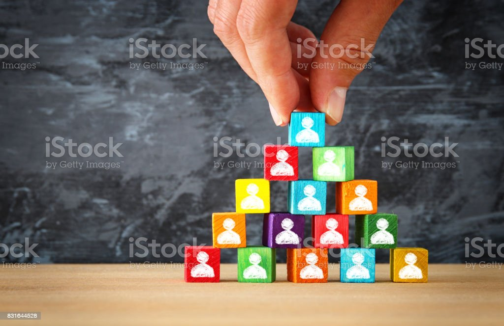 man's hand holding a top of wooden blocks pyramid with people icons over wooden table stock photo