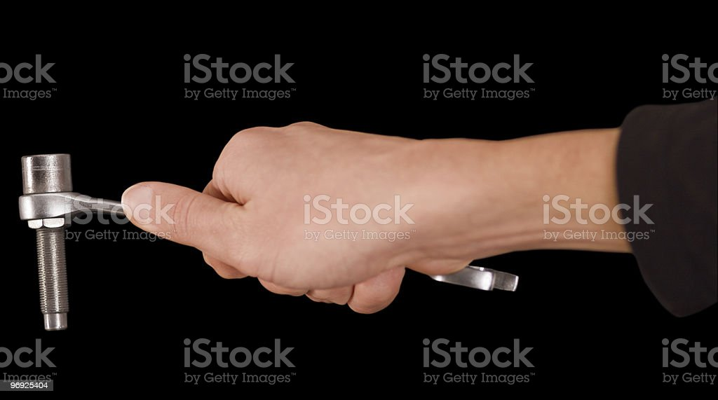 Man's hand holding a wrench isolated on black, clipping path royalty-free stock photo