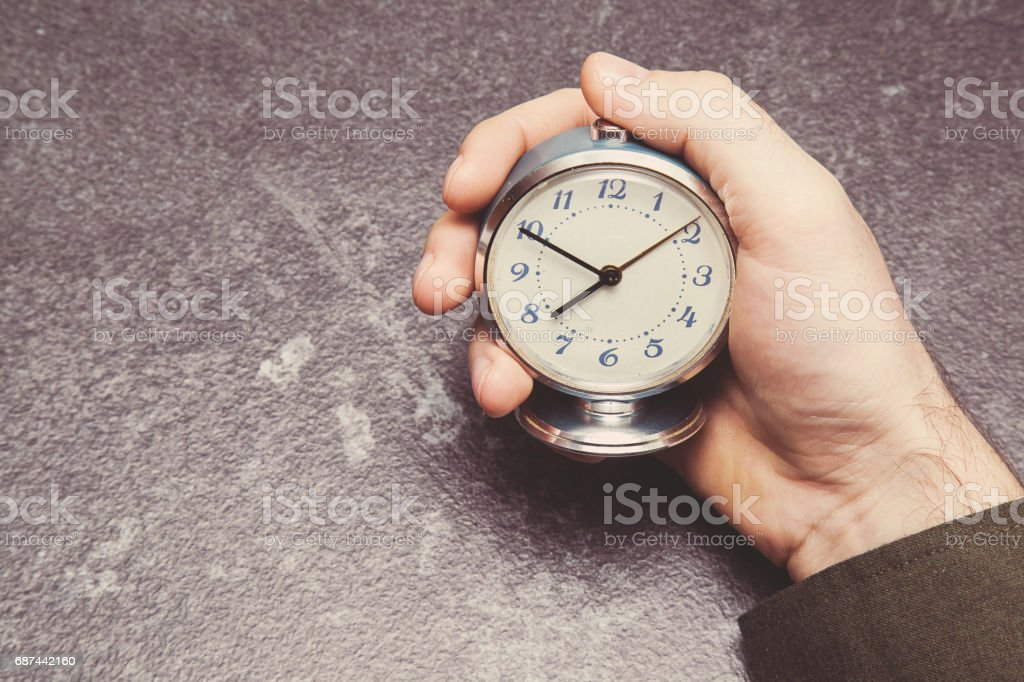 Man's hand holding an old table clock. Time tracking. Vintage retro style. stock photo