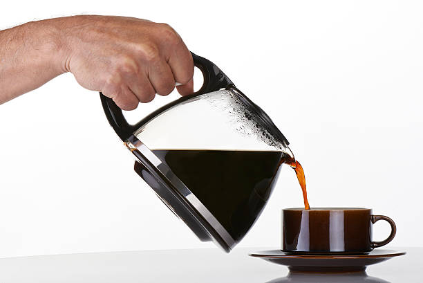 man's hand holding and pouring coffee into a brown cup man's hand holding and pouring coffee into a brown cup coffee pot stock pictures, royalty-free photos & images