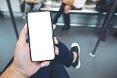 Mockup image of hand holding white mobile phone with blank black screen in subway