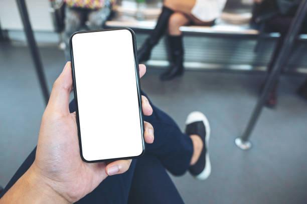 Die Hand des Mannes hält schwarzes Handy mit leerem Bildschirm in der U-Bahn – Foto