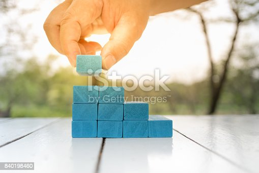 istock Man's hand holding blue wooden block on white wooden table. Building of steps, Learning and development concept. 840198460