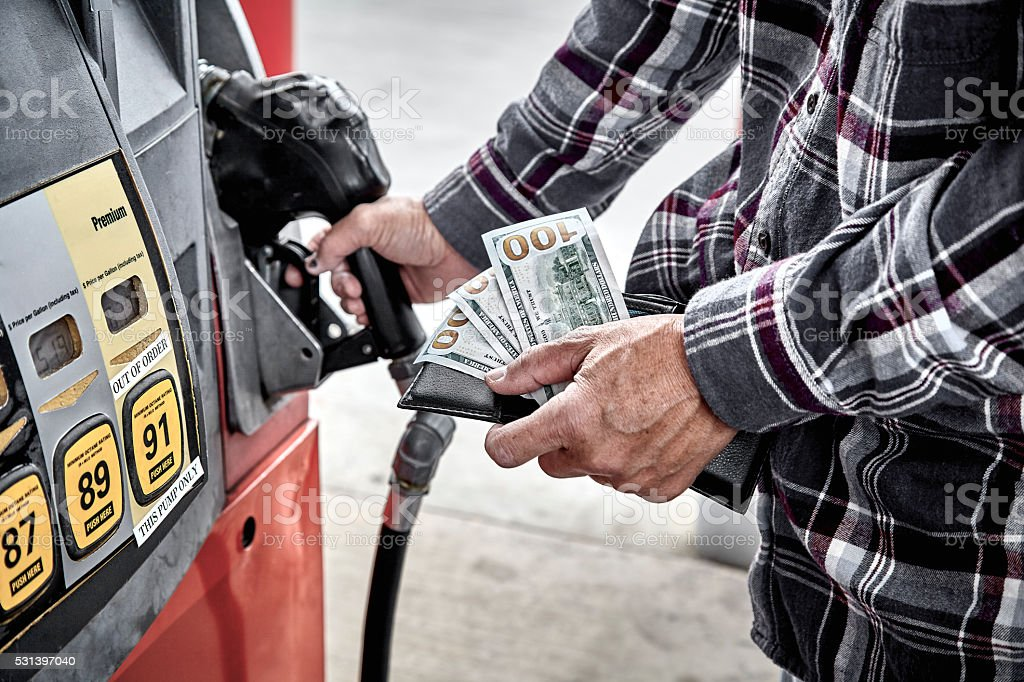 Mans Hand holding Cash while  preparing to Refuel Vehicle stock photo