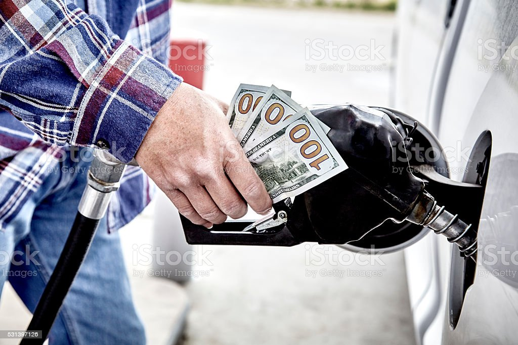 Mans Hand holding Cash while Refueling Vehicle stock photo