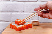 Man's hand holding chopsticks and eating sushi rolls on a wooden board.