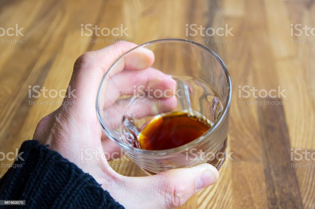 Man's hand holding glass with alcohol royalty-free stock photo