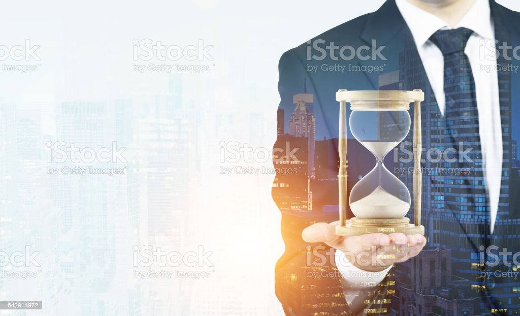 Man's hand holding hourglass, morning city stock photo
