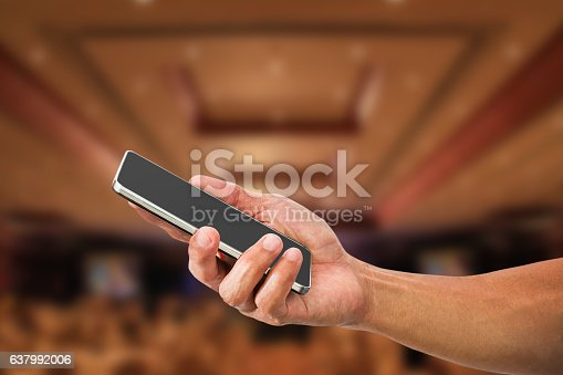 istock Man's hand holding mobile phone on blurred hotel lobby 637992006